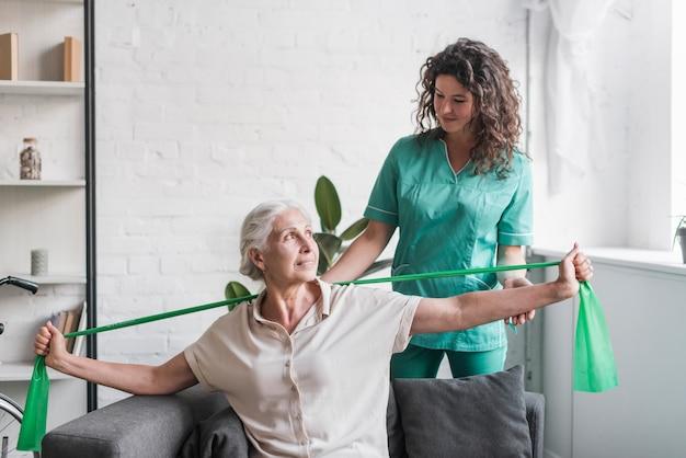 Ältere frau mit ausdehnungsband, das unterstützung durch weiblichen physiotherapeuten ist