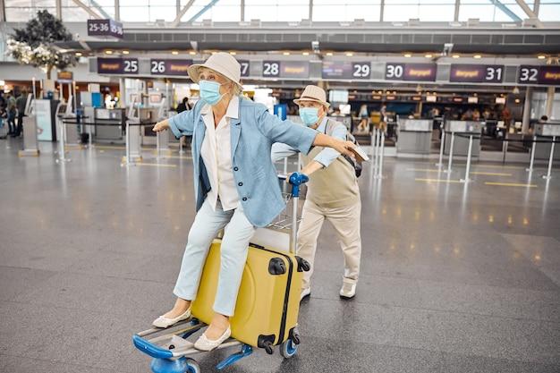 Ältere frau mit ausgestreckten armen genießt ihre fahrt auf einem gepäckwagen am flughafenterminal