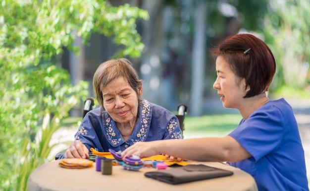 Ältere frau mit betreuerin in der nadel bastelt ergotherapie gegen alzheimer oder demenz