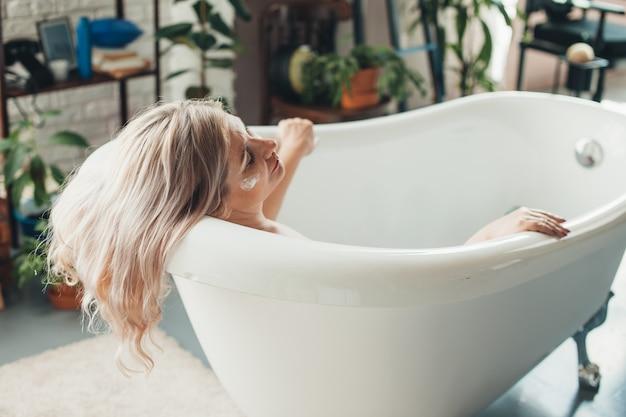 Ältere frau mit blonden haaren entspannt eine wanne mit einem spa-tag zu hause