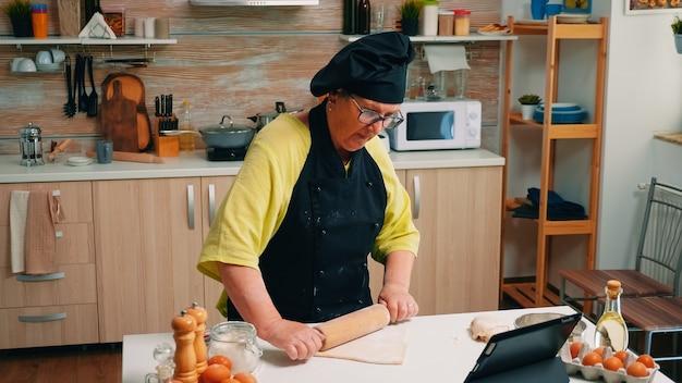 Ältere frau mit bonete, die rezept auf den digitalen laptop schaut. pensionierte dame, die kulinarischen ratschlägen auf dem tablet folgt, ein koch-tutorial in den sozialen medien lernt und den teig mit einem hölzernen nudelholz formt.