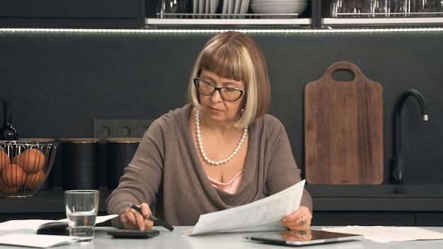 Ältere frau mit brille betrachtet ausgaben auf dem taschenrechner