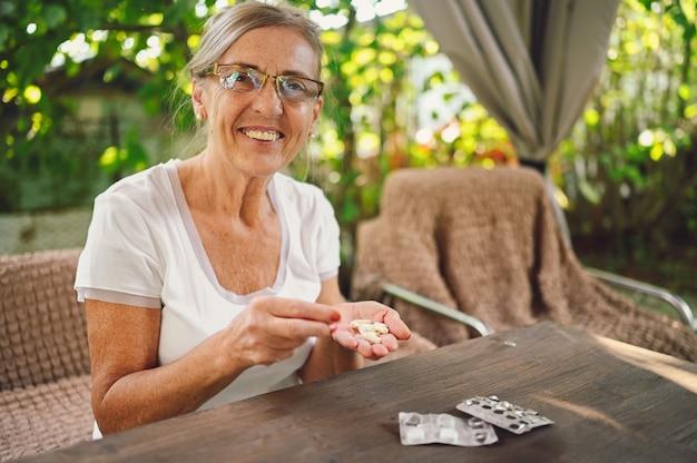 Ältere frau mit brille, die pillen nimmt