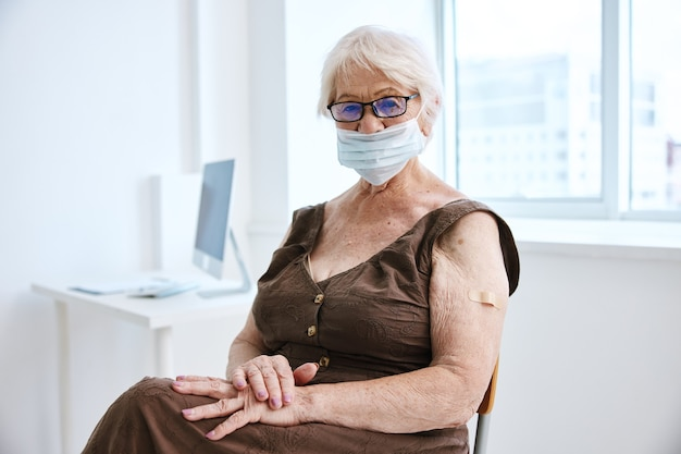 Ältere frau mit brille medizinische maske krankenhausimpfpass