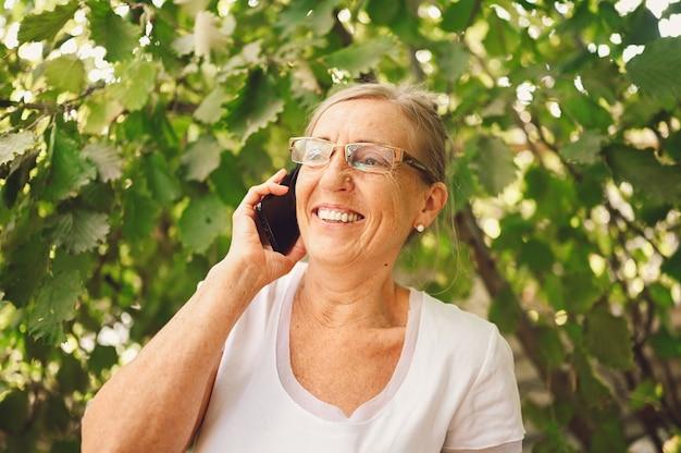 Ältere frau mit brille unter verwendung eines telefons