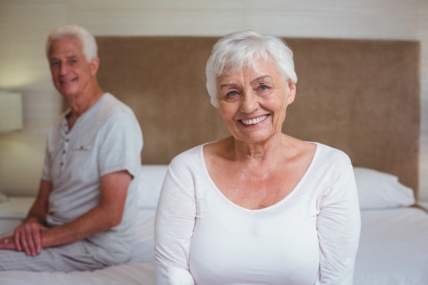 Ältere frau mit dem ehemann, der auf bett sitzt