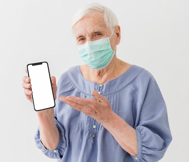 Ältere frau mit der medizinischen maske, die smartphone hält