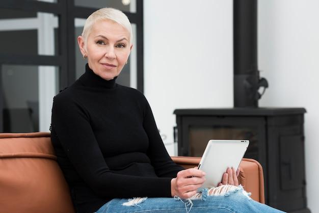 Ältere frau mit der tablette, die auf couch sich entspannt