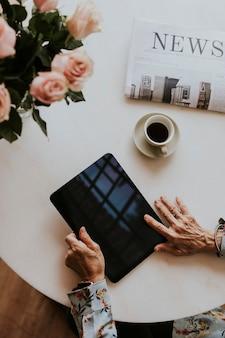 Ältere frau mit einem digitalen tablet