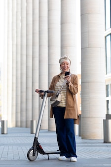 Ältere frau mit einem elektroroller in der stadt mit smartphone