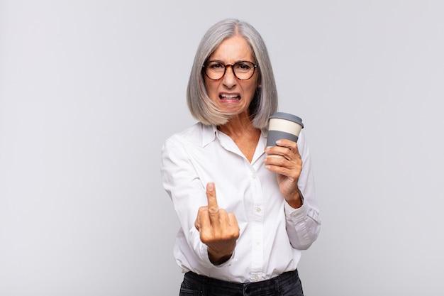 Ältere frau mit einem kaffee zum mitnehmen