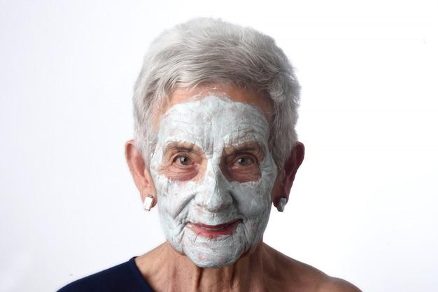 Ältere frau mit facian schablone auf weiß