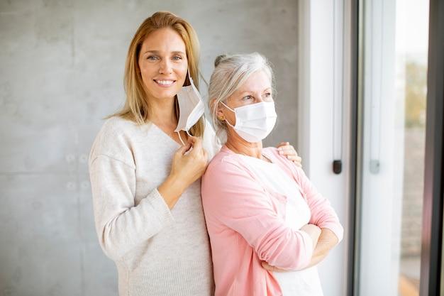 Ältere frau mit fürsorglicher tochter zu hause, die medizinische masken als schutz vor coronavirus trägt