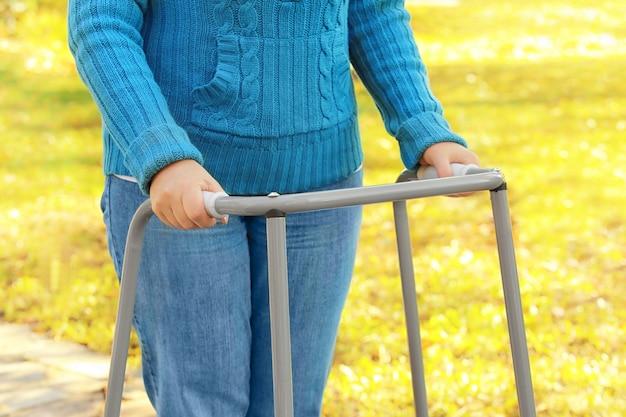 Ältere frau mit gehendem rahmen im park