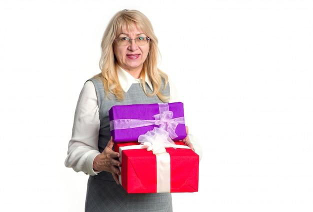Ältere frau mit geschenkkästen in ihren händen auf einem hellen hintergrund.