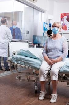 Ältere frau mit gesichtsmaske gegen covid 19, die am rand des krankenhausbettes sitzt und auf einen arzt mit krankheitsdiagnose wartet