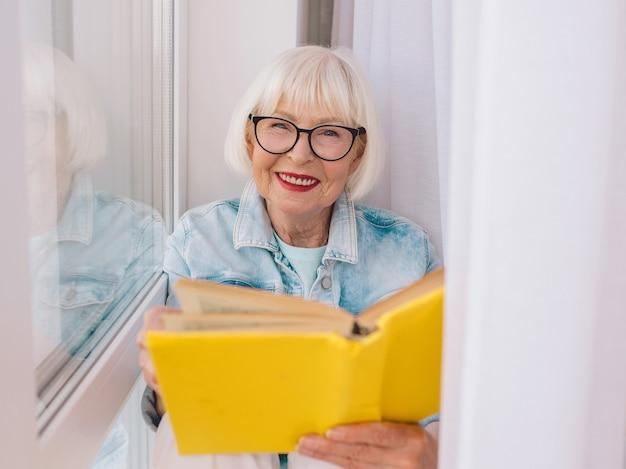 Ältere frau mit grauen haaren, die zu hause ein buch am fenster liest