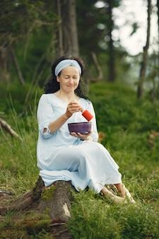 Ältere frau mit hinduistischen dingen. dame in einem blauen kleid. brünette sitzt.
