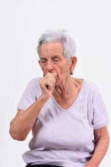Ältere frau mit husten auf weißem hintergrund