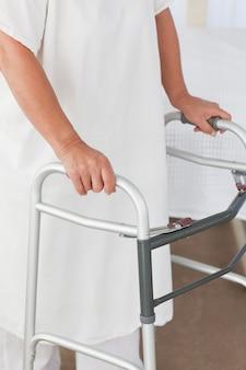 Ältere frau mit ihrem zimmerrahmen