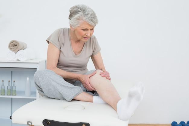 Ältere frau mit ihren händen auf einem schmerzhaften knie