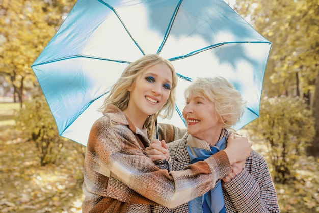 Ältere frau mit kleiner tochter im freien unter blauem regenschirm im herbstpark spazieren gehen