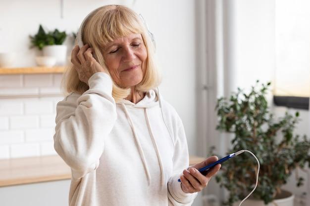 Ältere frau mit kopfhörern und smartphone zu hause