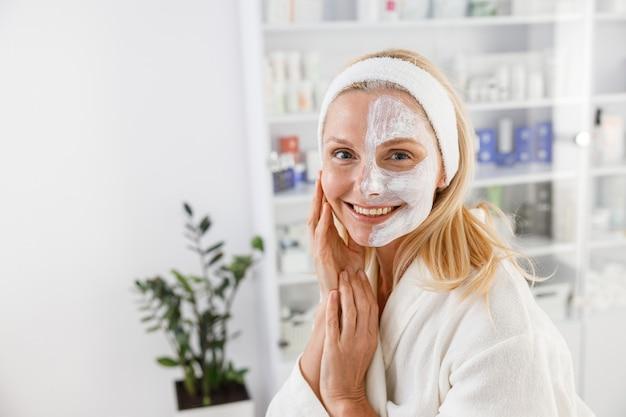 Ältere frau mit kosmetischer maske auf halbem gesicht im schönheitssalon.