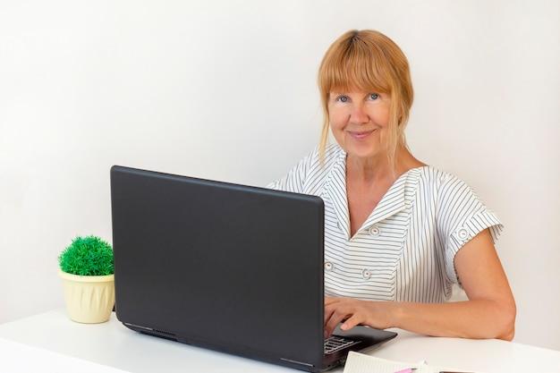 Ältere frau mit laptop. geschäftsfrau, die an einem laptop im büro arbeitet