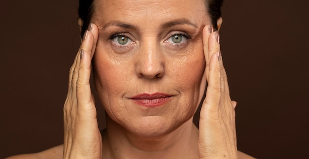 Ältere frau mit make-up beim posieren, während sie ihre schläfen hält