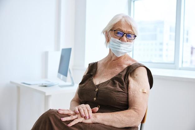 Ältere frau mit medizinischer maske bandaid-krankenhausgesundheit