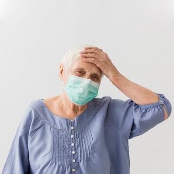 Ältere frau mit medizinischer maske, die fieber hat