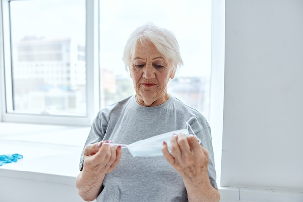 Ältere frau mit medizinischer maske in den händen krankenhaus-atemschutz. foto in hoher qualität