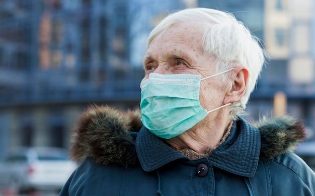 Ältere frau mit medizinischer maske in der stadt