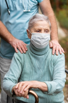 Ältere frau mit medizinischer maske und krankenschwester im pflegeheim