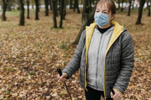 Ältere frau mit medizinischer maske und trekkingstöcken draußen