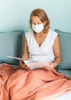 Ältere frau mit medizinischer maske zu hause während der pandemie beim lesen eines buches