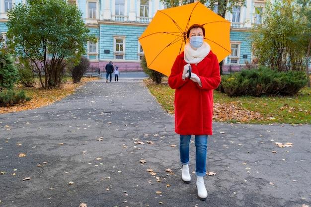 Ältere frau mit medizinischer schutzmaske auf ihrem gesicht geht im herbstpark mit orangefarbenem regenschirm.