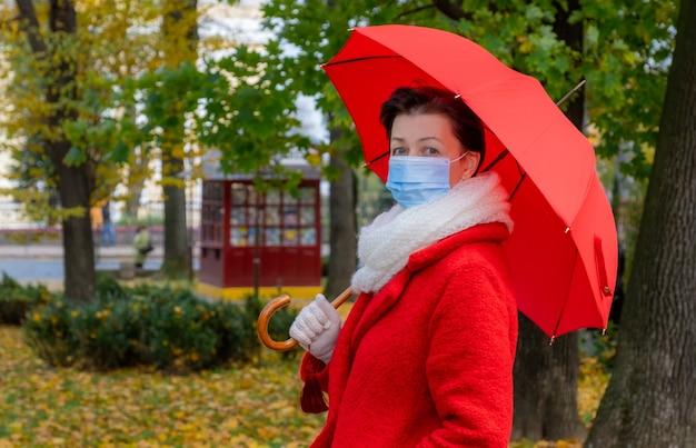 Ältere frau mit medizinischer schutzmaske auf ihrem gesicht geht im herbstpark mit rotem regenschirm.