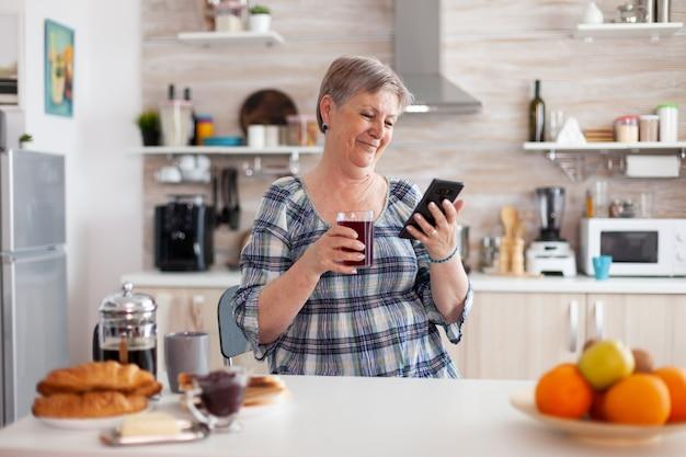 Ältere frau mit mobilem gerät in der küche, die morgens während des frühstücks aromatischen tee trinkt. authentische ältere person, die nach moderner smartphone-internettechnologie sucht, seniorenfreizeit