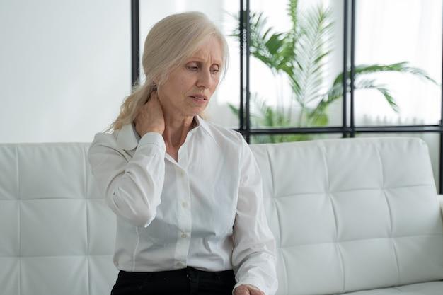 Ältere frau mit nackenschmerzen, die zu hause auf der couch sitzt