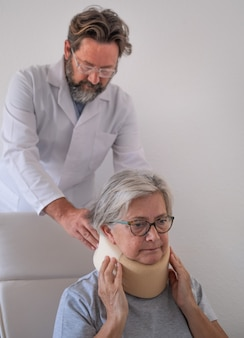 Ältere frau mit schmerzen, die mit hilfe ihres physiotherapeuten einen halskragen trägt