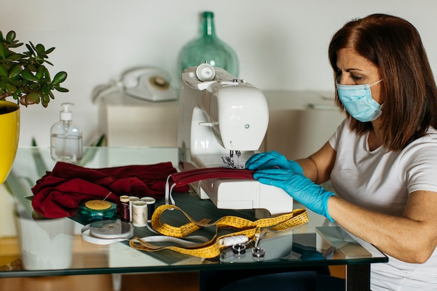 Ältere frau mit schutzausrüstung, die stoffgesichtsmasken näht