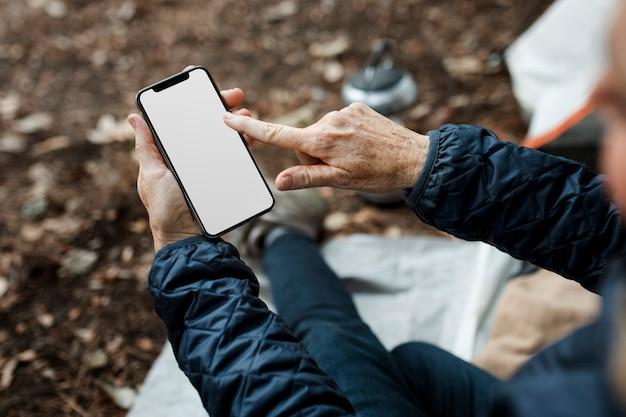 Ältere frau mit smartphone mit weißem bildschirm