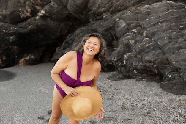 Ältere frau mit strohhut, die ihren tag am strand genießt
