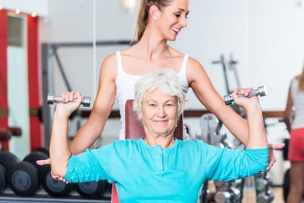 Ältere frau mit trainer in anhebendem dummkopf der turnhalle