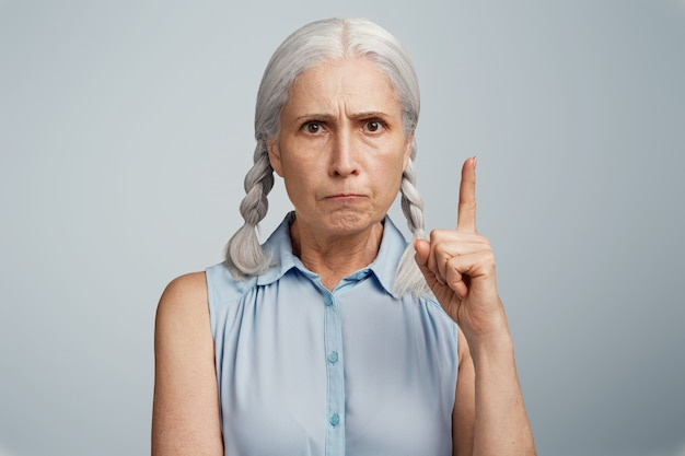Ältere frau mit zöpfen in blauer bluse gekleidet