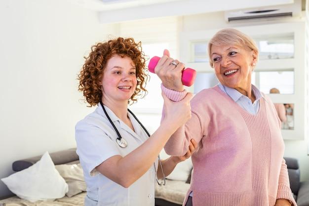 Ältere frau nach schlaganfall im pflegeheim, die mit professionellem physiotherapeuten trainiert.