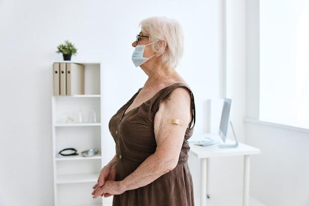 Ältere frau pflaster auf ihrem arm krankenhaus covid-impfung