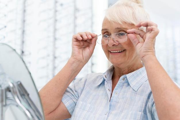 Ältere frau probiert eine neue brille an